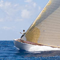 The bow man of the J class yacht Ranger, directs the helmsman using hand signals at Antigua Classic Yacht Regatta. The yacht race is one of the worlds most prestigious traditional yacht races. .The J class yacht Ranger is a replica of a 1920s era racing sailboat.