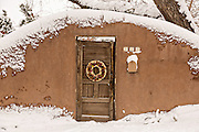 A traditional door on an adobe style home in the Arroyo Tierra Blanca neighborhood after a winter snowfall in Santa Fe, New Mexico.