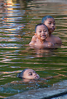Three children swimming in the sacred lake at sunset in Candidasa, Bali, Indonesia