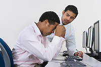 Two business men at desk in front of computer