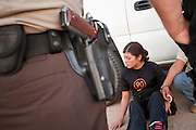 17 MAY 2006 - GILA BEND, AZ: A woman arrested by MCSO deputies in rural Maricopa county awaits transport to the county jail. Deputies from the Maricopa County Sheriff's Department run an anti-smuggling operation along I-8 near Gila Bend, AZ. Deputies arrested 12 illegal immigrants from Mexico during the operation. PHOTO BY JACK KURTZ
