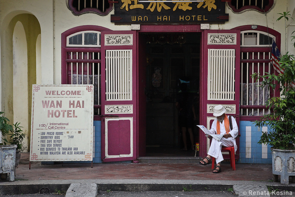 A man sits down to read a newspaper at hotel front in the center of Georgetown's old colonial district. It is located on the island of Penang, Malaysia.
