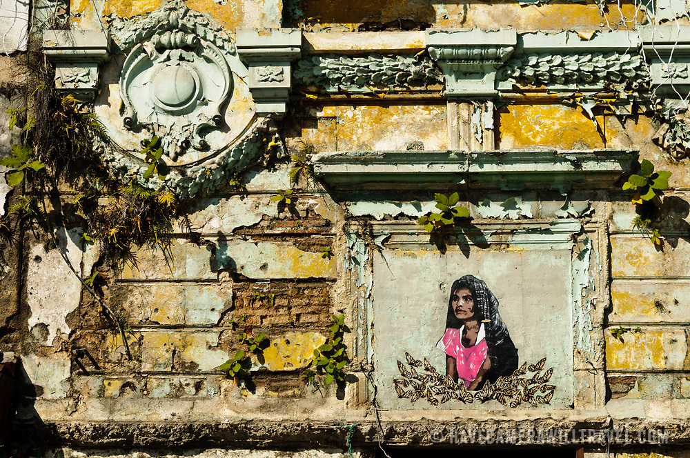 Architectural detail of a rundown colonial building with painting of a woman in downtown Guatemala City, Guatemala.
