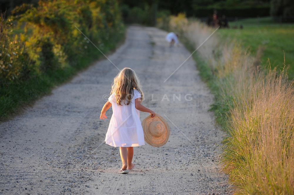 little girl in a pretty dress walking down a dirt road in The Hamptons