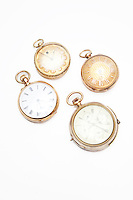 Four old-fashioned pocket watches over white background