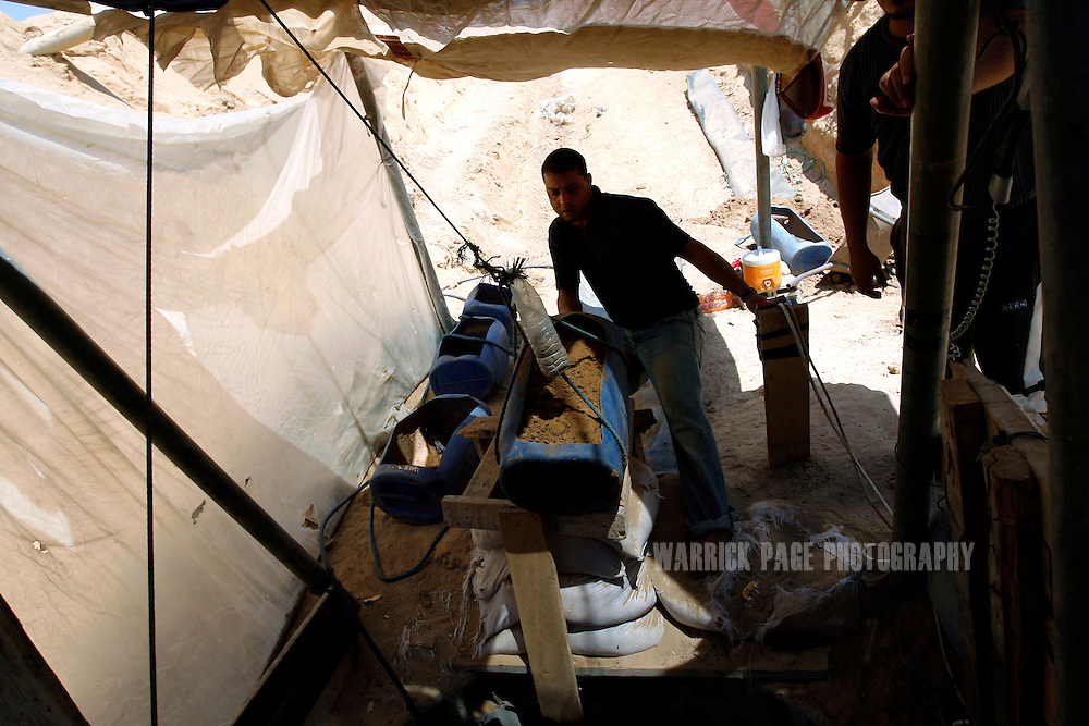 RAFAH, GAZA STRIP - JUNE 10: A Palestinian tunnel worker repairs a badly damaged tunnel destroyed during Operation Cast Lead, on Wednesday June 10, 2009, in Rafah, Gaza Strip. The tunnels previously built to smuggle weapons in from Egypt, now number in the hundreds after the Israeli government enforced a blockade on Gaza in 2007. Hundreds of tunnels line the Rafah/Egypt border operating non-stop as Palestinians smuggle food, fuel, livestock, motorcycles, medicine in addition to weapons. The Israeli airforce has been unsuccessful in halting the smuggling, in spite of repeated bombings. Tunnel workers are warned in advance of pending bombings by Egyptian police who receive advance notice of bombing operations from the Israelis. Tunnel workers are paid approximately USD 20-40 per day for a 14 hour day, while HAMAS charges USD 2500 for the permit to build a tunnel and takes 50% of all sales made. A completed tunnel costs between USD 70,000 and 90,000. (Photo by Warrick Page)