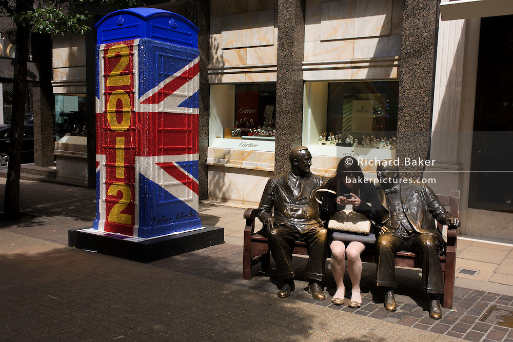 London 19/6/12. A woman texts with statues of F.D. Roosevelt & Winston Churchill on a bench in Bond Street nr the ?Union Jack 2012? replica artbox phone kiosk by Sir Peter Blake (artist of the Beatles 'Sergeant Pepper') and part of an art project for the Queen's Diamond Jubilee and Olympics.
