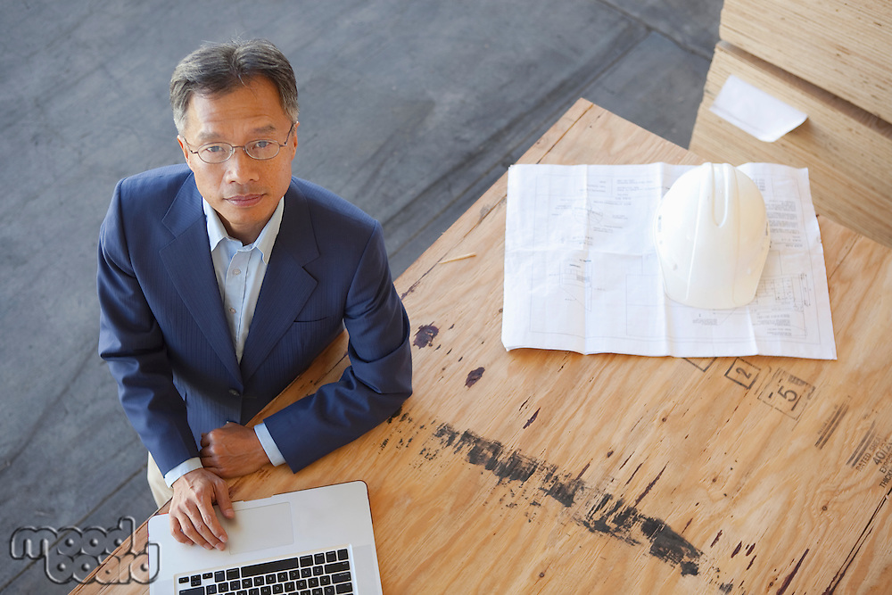 Top view of manager using laptop on plywood in warehouse