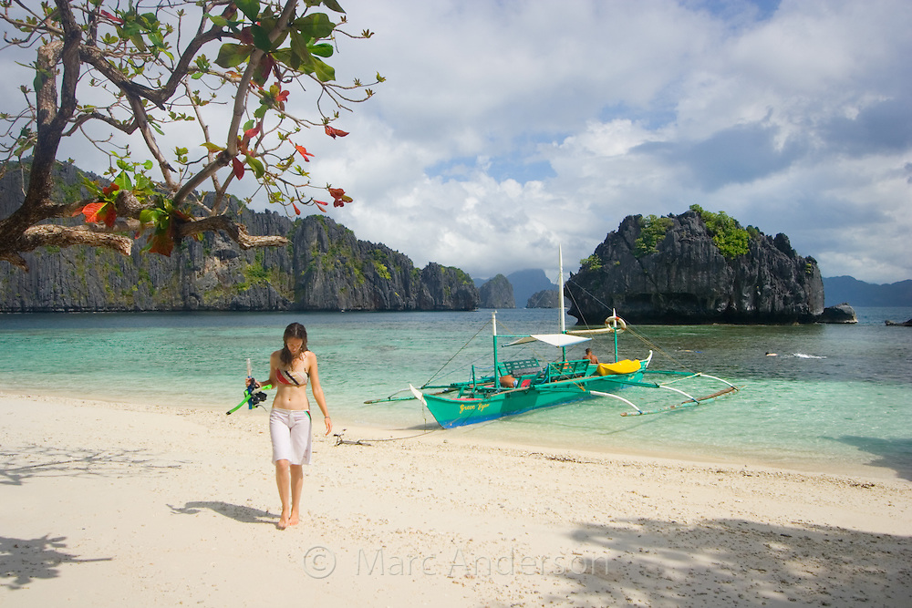 A woman walking on a white sandy beach on a tropical island in the Bacuit Archipelago, Palawan, Philippines