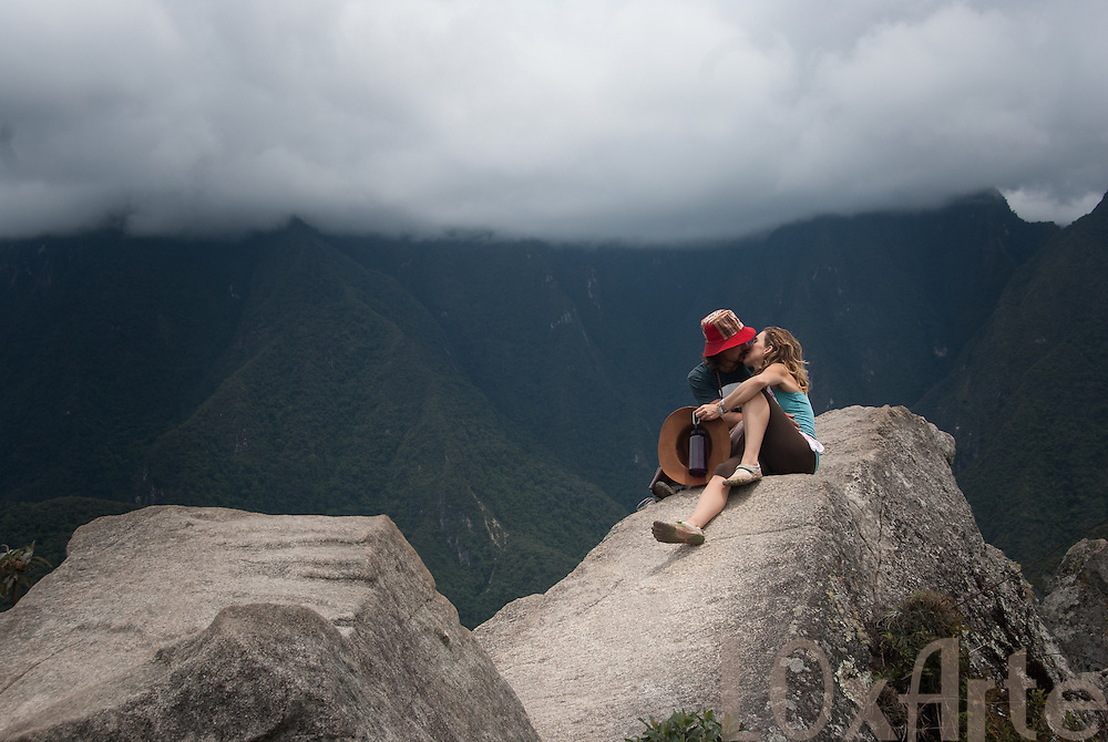 A couple kissing on the highest rock on Huayna Picchu, Machu Picchu, Peru with a low lying cloud behind them.<br />