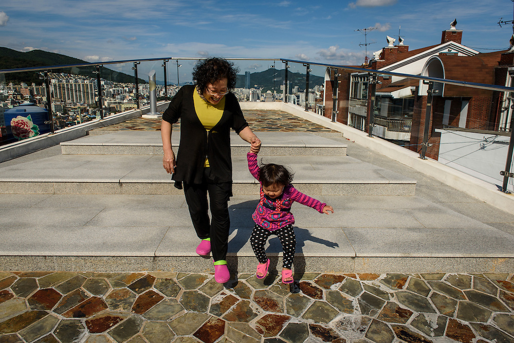 A child and grandmother play on an observation deck on Ibagu-gil in Busan, South Korea.