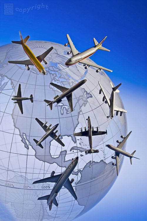 Model airplanes facing in all directions cover a glass globe.