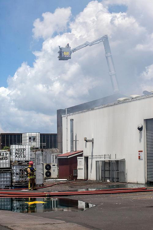 Fire fighters at the scene of a third alarm fire in a factory started amongst a stack of pallets next to the main building, Wharf Road, Te Atatu, Auckland, New Zealand, Sunday, December 15, 2013. The original fire was near a hazardous chemicals bunker, but was not a concern. Credit:SNPA / Bradley Ambrose