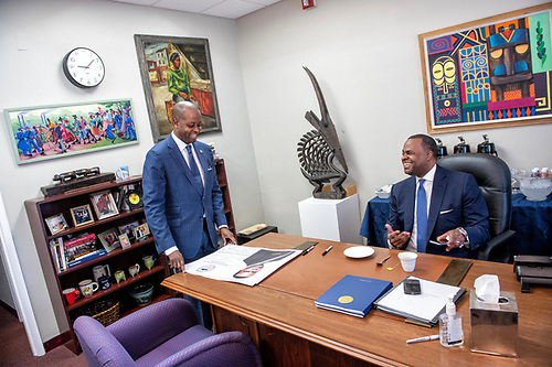 Howard University president Wayne A.I. Frederick speaking to 2019 Commencement speaker Kasim Reed in an office setting.