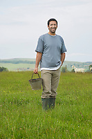 Man holding bucket in field portrait