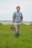 Man holding bucket in field portrait