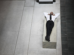 June 17, 2010 - A view looking down on a businessman taking a break laying down on a bench. (Credit Image: © Mint Images via ZUMA Wire)