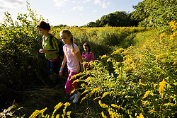 A woman and two girls walk in a field at the Pell Farm in Grafton, Massachusetts.