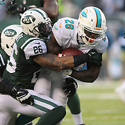 Lamar Miller, Miami Dolphins, is tackled by Dawan Landry, New York Jets, during the New York Jets Vs Miami Dolphins  NFL American Football game at MetLife Stadium, East Rutherford, NJ, USA. 1st December 2013. Photo Tim Clayton