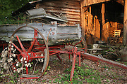 An abandoned, broken down horse drawn, wooden wheeled farm wagon sitting in front of an old abandoned backwoods house.