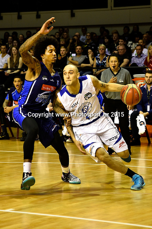 Lindsay Tait (R of the Saints dribbles the ball with DeRonn Scott of the Giants during the NBL semi final basketball match between Wellington Saints and Nelson at the TSB Arena in Wellington on Saturday the 4th of July 2015. Copyright photo by Marty Melville / www.Photosport.nz