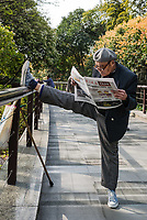 Shanghai, China - April 7, 2013: one old man exercising stretching splits and reading newspaper in gucheng park at the city of Shanghai in China on april 7th, 2013