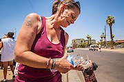 "20 JUNE 2012, PHOENIX, AZ:  A homeless woman pours water into her bottle in Phoenix, AZ, Wednesday. June 20 is the first day of summer in the northern hemisphere. The high temperature in Phoenix Wednesday soared to over 110 (F), well above the normal of 105. The hot weather is especially stressful on the homeless, who don't have the opportunity to get into air conditioning or access to cold water. ""I Will Listen,"" an outreach organization that assists the homeless and community of street people in Phoenix, AZ, provides free food and cold drinks to the homeless in central Phoenix. They ran out of drinks and food in about one hour during Wednesday's outreach.        PHOTO BY JACK KURTZ"