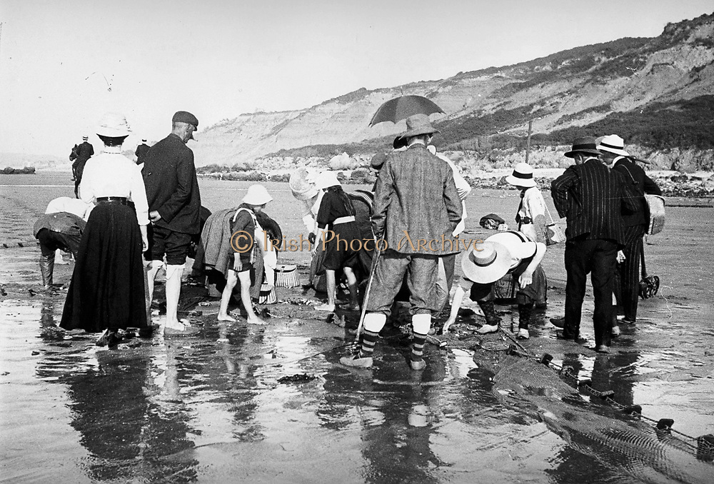 French coastal scene showing young children and adults searching a beach for shellfish or crabs. Circa 1900