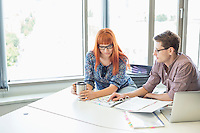 Creative business colleagues reading file together at desk in office