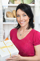 Portrait of a beautiful female holding cake box in shop