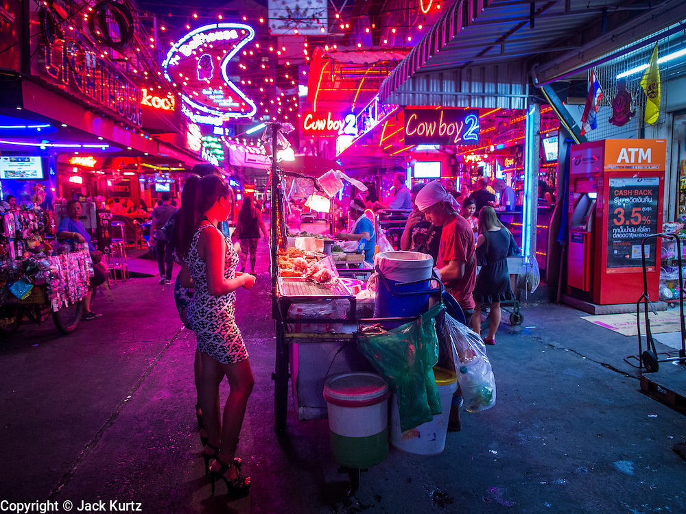 "22 MAY 2014 - BANGKOK, THAILAND:  A food vendor does business on Soi Cowboy, one of Bangkok's ""adult entertainment"" districts, after the army announced a coup and overnight curfew. The Thai army suspended civilian rule, suspended the constitution and declared the ""military takeover of the nation."" The announcement came just before evening as a meeting between civilian politicians and the army was breaking up with no progress towards resolving the country's political impasse. Civilian politicians were arrested when the meeting ended. The army also declared a curfew from 10PM until 5AM.   PHOTO BY JACK KURTZ"