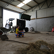 Adam Doran, son of Irish farmer Enda Doran, plays with a miniature tractor in their farm's workshop in Ballinasloe, Co. Galway...Mr. Doran is the eldest of 3 brothers and sisters and by tradition the heritor of the family farming land and business. His farming activities involve cereal and potato production, cattle and sheep breathing and contract work for other farmers.