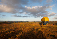 A hot air balloon prepares for take off in a field north of Cairns.