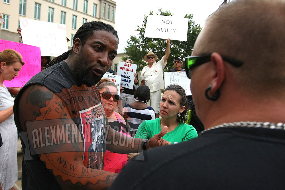 Two citizens argue the guilt of George Zimmerman, prior to the murder trial at the Seminole County Courthouse on Saturday, July 13, 2013, in Sanford, Florida.  Zimmerman had been charged for the 2012 shooting death of Trayvon Martin and was found not guilty by a jury of six women. The protests on the grounds ended peacefully after the verdict was read. (AP Photo/Alex Menendez)
