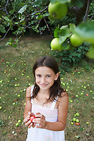 Girl (10-12) holding apple in garden
