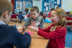 Primary schoolchildren role playing different careers UK