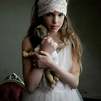 girl holding an old doll in a room of decay
