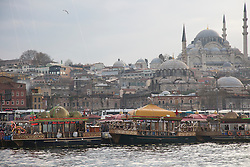 Boats along the Golden Horn prepare fish sandwiches, known in Turkish as balik ekmek. Beyond the boats is the Suleymaniye Mosque.
