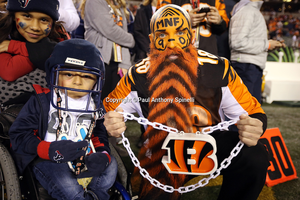 A trio of Cincinnati Bengals and Houston Texans fans pose for a photo before the 2015 week 10 regular season NFL football game against the Houston Texans on Monday, Nov. 16, 2015 in Cincinnati. The Texans won the game 10-6. (©Paul Anthony Spinelli)
