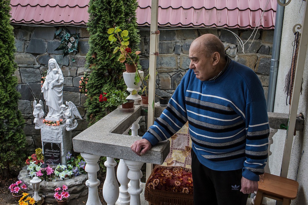 SKOLE, UKRAINE - MAY 1, 2015: Dmitry D. Boiko, 76, one of the current residents of a house that during World War II served as the local headquarters of the NKVD, a Soviet secret police agency, and which is believed to contain a well in the basement in which the bodies of Ukrainian partisans were dumped, poses for a portrait outside the house in Skole, Ukraine. The organization Dolya was formed to excavate and repatriate remains from World War II, though its focus is often on locating the graves of Ukrainian partisans killed by Soviet forces. CREDIT: Brendan Hoffman for The New York Times