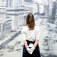 London, UK - 12 April 2013: A Sotheby's employee poses in front of Gerard Richter's photo-realist masterwork (Est. $30-40 million). The work will go on sale at Sotheby's New York in May 2013. The Blockbuster sales at include works by Richter, Modigliani, Picasso, Rodin, Bacon, Cezanne.