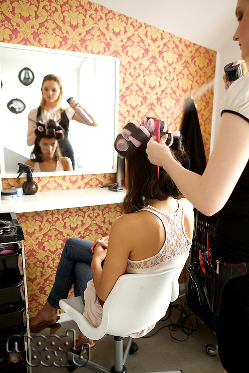 Female hairdresser spraying hairspray in customer's hair