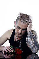 studio shot of a sad romantic  man  with tatoos and piercing