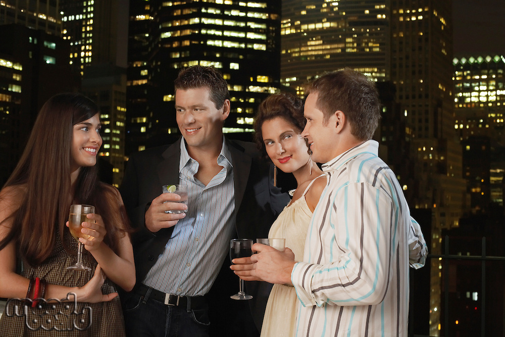 Two couples drinking together against night city skyline