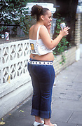 A fat chav girl drinking a beer and smoking a fag, whilst talking on a mobile phone, Notting Hill Carnival, London, UK 2004