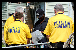 March 6th,2006. New Orleans, Louisiana. Six months after hurricane Katrina devasted the Lower 9th Ward, recovery work, slow and sometimes grim, continues at what appears to be a snail's pace. Volunteer Chaplains from Victim Relief in Texas perform a simple ceremony over the remains of a resident of the Lower 9th Ward discovered in a house. The house had previously been searched and a body removed, however it appears the initial removal process missed some of the remains which were today placed in a plastic bag and taken away by the coroners office.