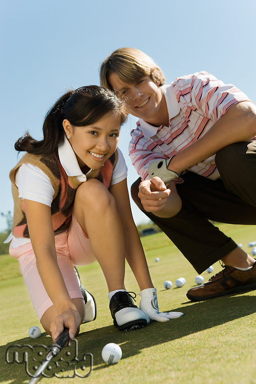 Golfer and Instructor Eyeing Putt