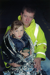 Young girl wrapped in silver blanket being comforted by worker from emergency services,