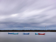 Canoes float tethered in evening breeze in a tidal pond on the English Coast at Saint Annes near Blackpool