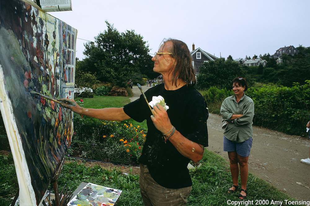 MONHEGAN ISLAND, MAINE - AUGUST 02: Ted Tihansky paints flowers as onlookers gather to watch, August 2, 2000 on Monhegan Island, Maine. Monhegan Island, home to lobstermen and painters and a popular destination for tourists is twelve miles off the coast of Maine. Ringed by high, dark cliffs, its interior a mix of meadows, marsh and spruce groves, Monhegan is one of just 14 true island communities left off the coast of Maine. The island has a 65 permanent, year-round residents and the population grows to around 200 in the summer, with day-trippers adding several hundred more. (Photo by Amy Toensing) _________________________________________<br /> <br /> For stock or print inquires, please email us at studio@moyer-toensing.com.